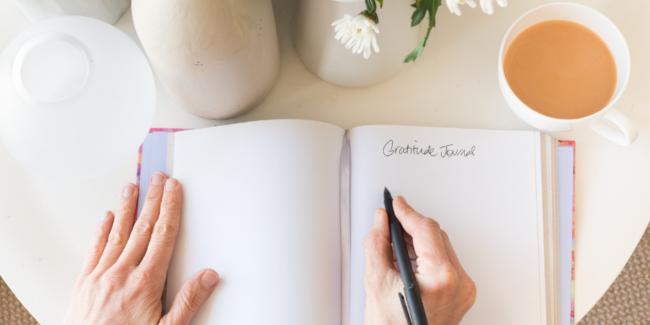 carnet de gratitude ouvert sur une page blanche, une tasse de thé et un vase avec des fleurs